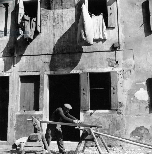 A carpenter carving in the street, Chioggia, Italy, March 1954 (b/w photo)