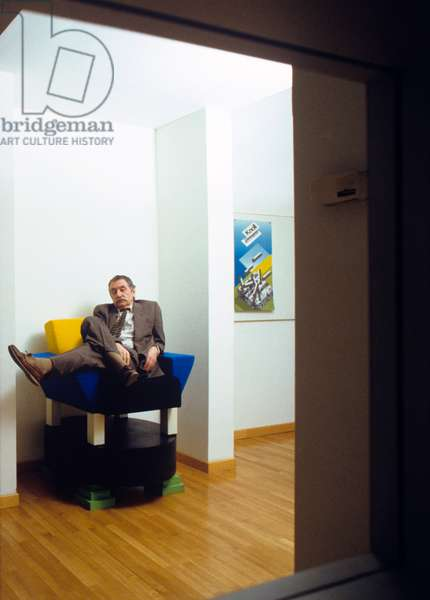 The architect Ettore Sottsass sitting on his own armchair (photo)