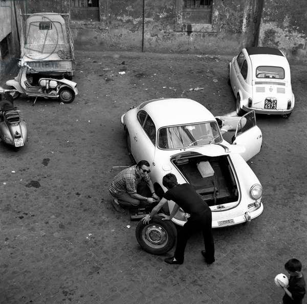 Three men changing car wheels, Italy