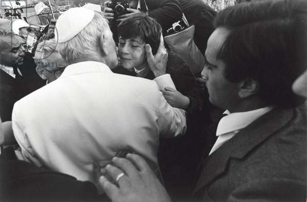Pope John Paul II is kissing a young boy during a visit to the villages struck by the earthquake of 1980