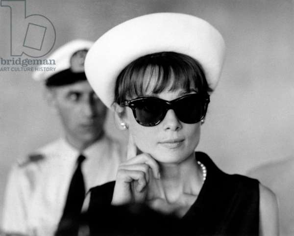 Audrey Hepburn wearing big sunglasses at the airport of Paris, 1962 (b/w photo)
