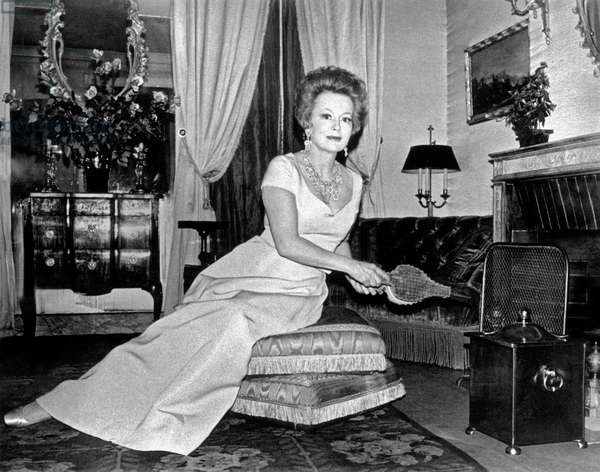 Olivia de Havilland posing in front of the fireplace