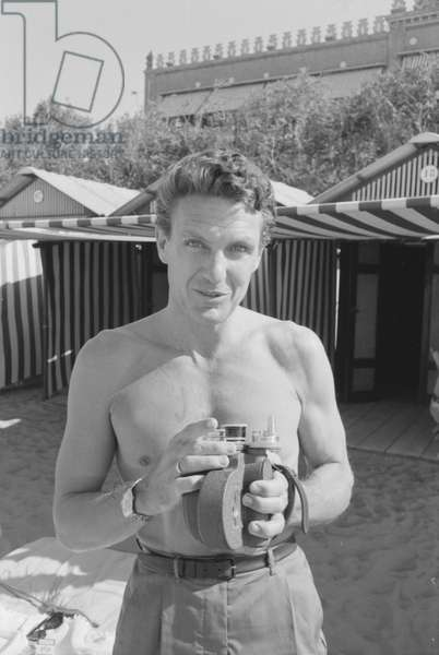 Robert Stack holding a portable camera, Italy, 1958 (b/w photo)