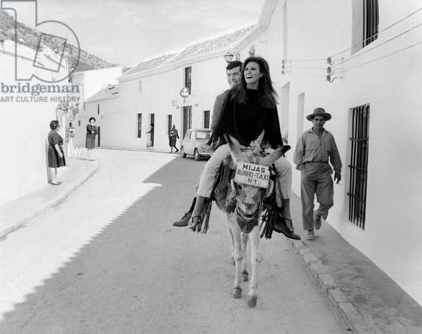 Raquel Welch and Patrick Curtis riding a donkey in Malaga, 1966 (b/w photo)