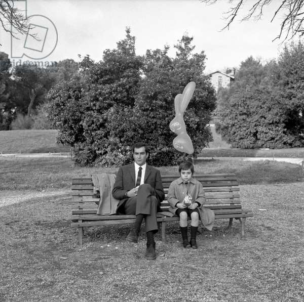 A father and a son sitting on a bench at the park, Italy