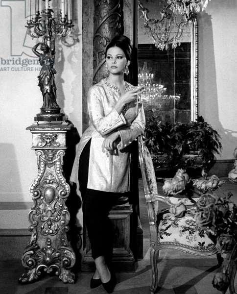 Claudia Cardinale posing in a scene dress, 1963 (b/w photo)