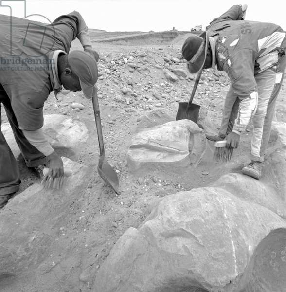 Two workers digging with a shovel in a mine to find diamonds, Republic of South Africa, 1965 (b/w photo)