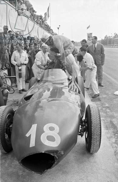 American car driver Harry Schell jumping into the Vanwall race car number 18 at the autogrome for the Italian Grand Prix, Monza, Italy, 2nd September 1956 (b/w photo)