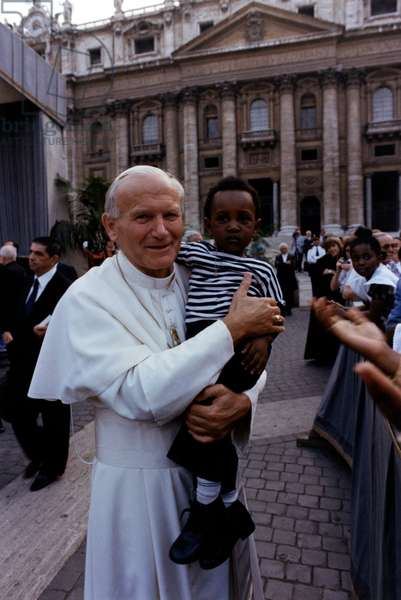 Pope John Paul II holding a child in his arms