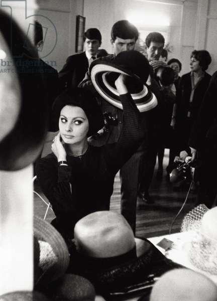 Sophia Loren posing in front of a mirror in a hats shop, 1963 (b/w photo)