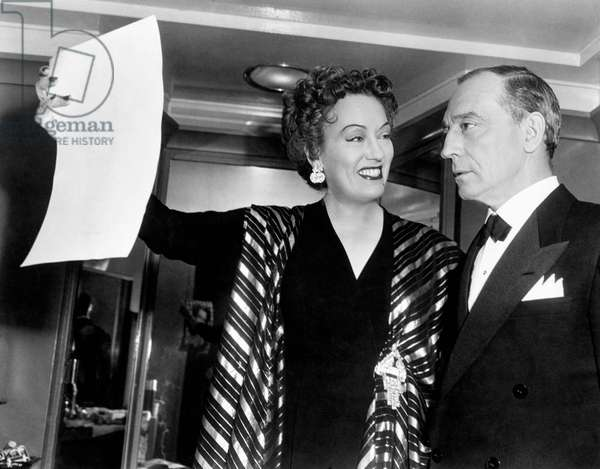 Gloria Swanson shows a photograph to Buster Keaton
