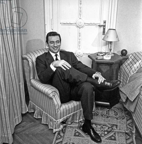Yves Montand sitting on an armchair, 1958 (b/w photo)