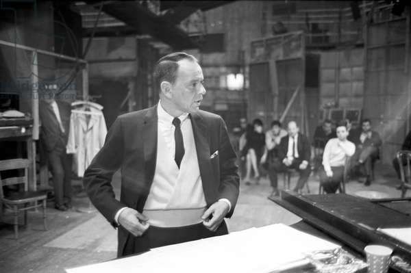 Frank Sinatra tidying his waistcoat in a break while rehearsing his show, 1964 (b/w photo)