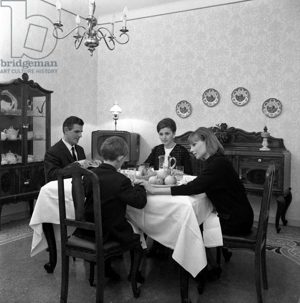 A foreigner baby sitter eating with an Italian family, Italy, 1960s