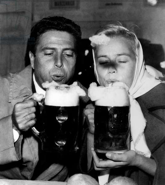 Maria Schell and Raf Vallone in front of two beer mugs, 1956 (b/w photo)
