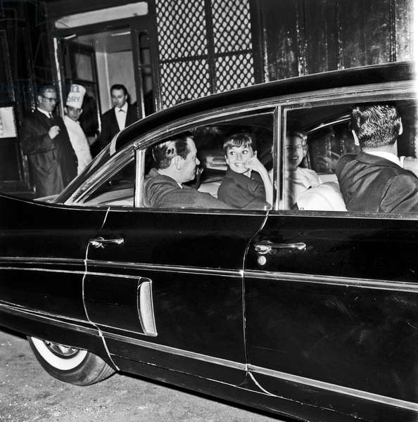 Audrey Hepburn in a car with William Holden and Curd Jurgens, Paris, France, 1962 (b/w photo)