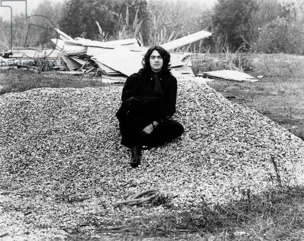 Riccardo Fogli sits on a stones drift