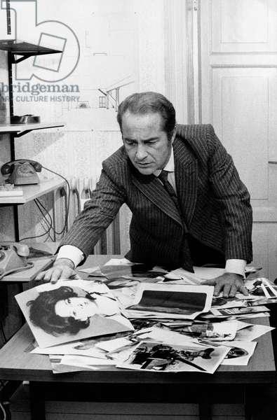 Rossano Brazzi watching some photos , 1970s (b/w photo)