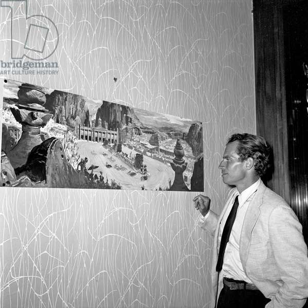 Charlton Heston admiring a sketch of the set design for the film 'Ben Hur', Rome, Italy, 1958 (b/w photo)