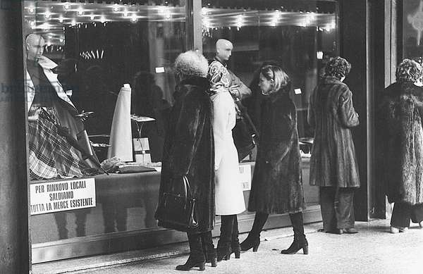 Women watching the window of a shop displaying goods on clearance sale, Milan, 1979 (photo)
