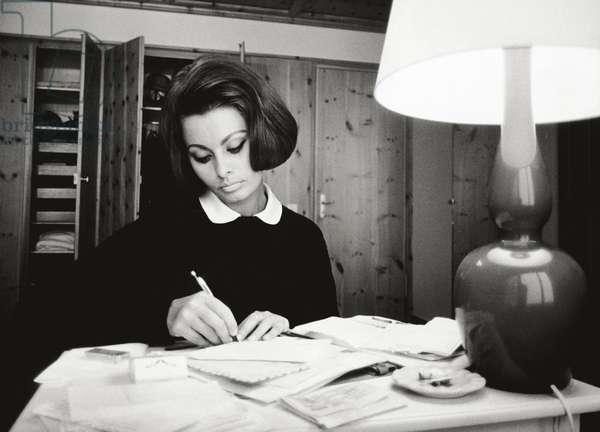Sophia Loren in her lodge in Switzerland is writing some letters, 1963 (b/w photo)