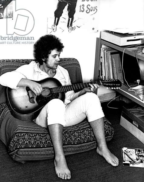 Lucio Battisti playing the guitar wearing pyjamas