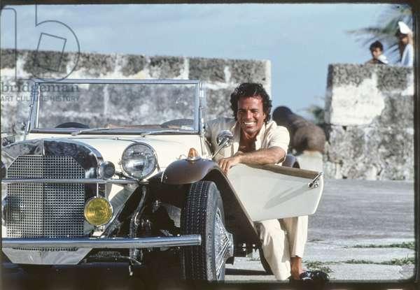 Julio Iglesias leaning on a vintage car