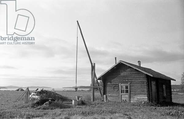 A solitary typical Finnish wooden house built in the middle of a field, Finland, 1960s (b/w photo)