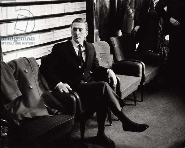 The actor Kirk Douglas is sat on an armchair (b/w photo)