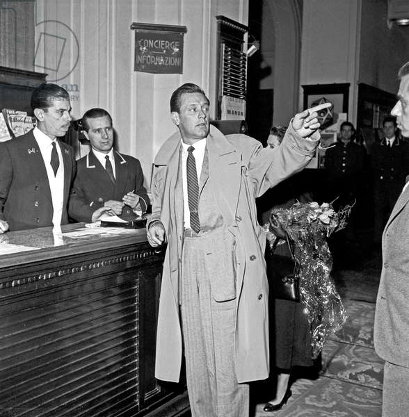 William Holden talking to the receptionists of his hotel, Rome, Italy, 1957 (b/w photo)