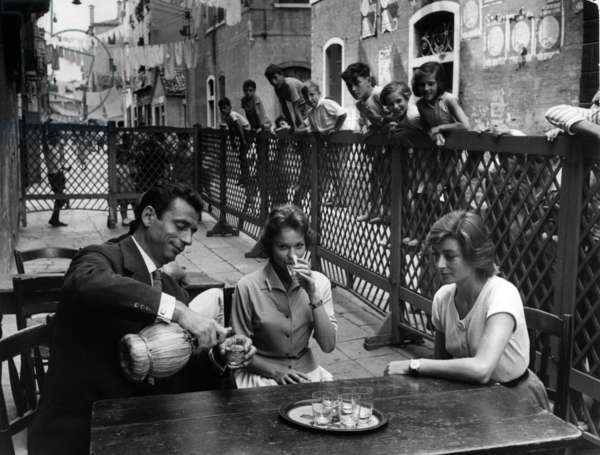 Yves Montand, Francoise Arnoul and Anouk Aimee sitting at a table
