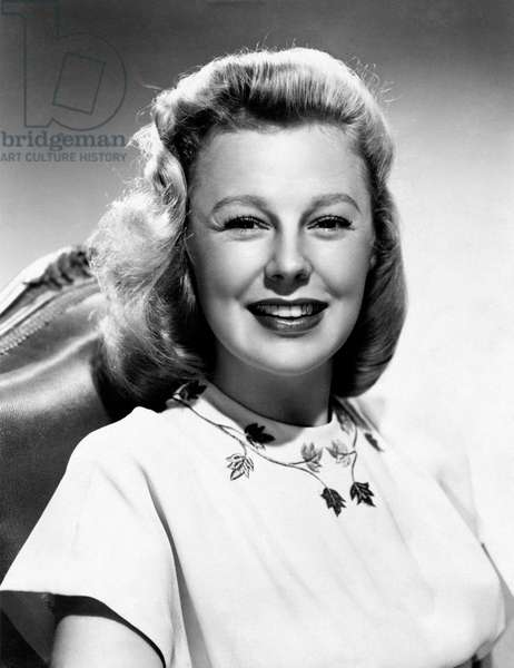 A smiling June Allyson, poses