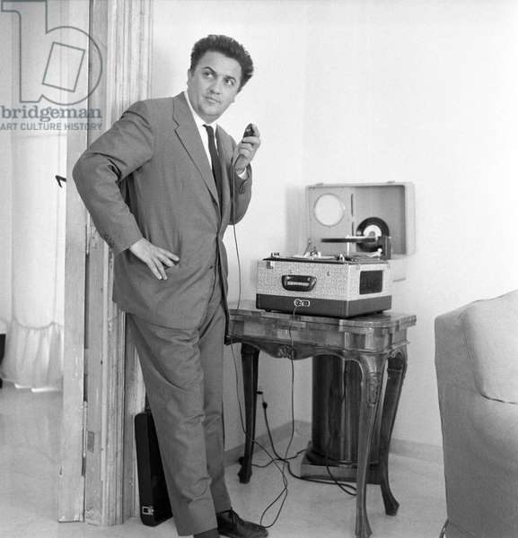 Federico Fellini beside a record player, Italy, 1957 (b/w photo)