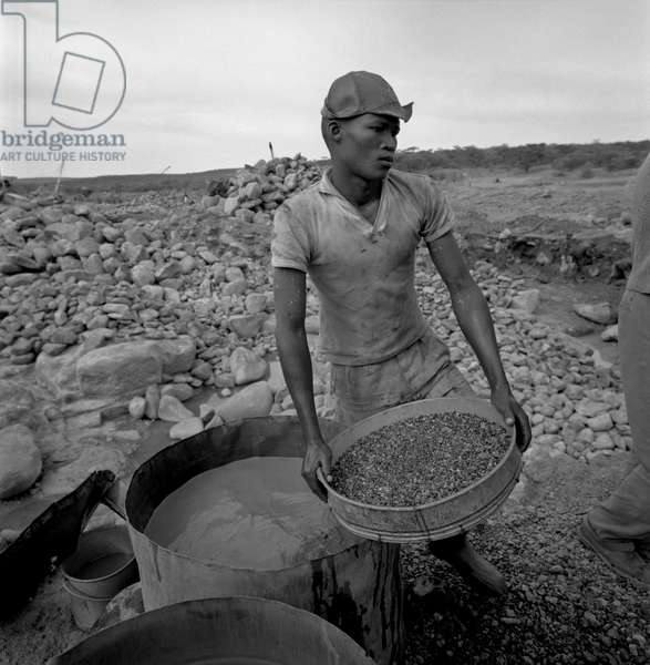 A boy sifting the soil in a diamond mine, Republic of South Africa, 1965 (b/w photo)