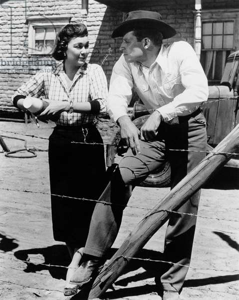 Jane Wyman and Charlton Heston leaning on a barbed wire fencing