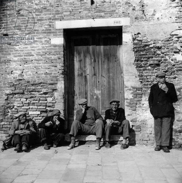 Some elderly fishermen taking a rest under the sun, Chioggia, Italy, March 1954 (b/w photo)