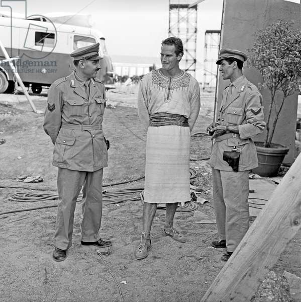 Charlton Heston speaking with two policemen on the movie set, Rome, Italy, 1958 (b/w photo)