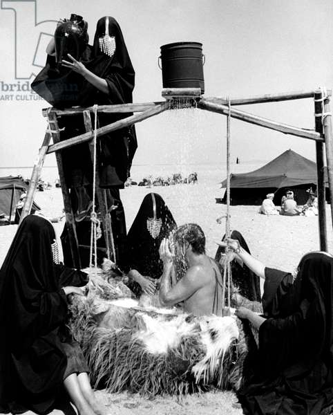 Terence Stamp washes helped by some women, 1966 (b/w photo)