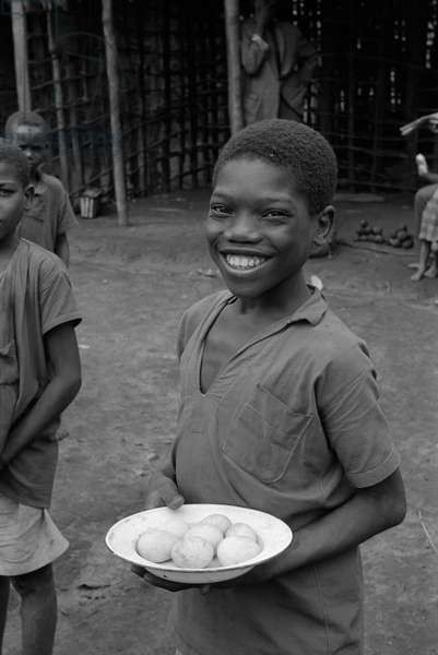 Smiling African kid posing holding a plate of eggs, Africa, April 1965 (b/w photo)