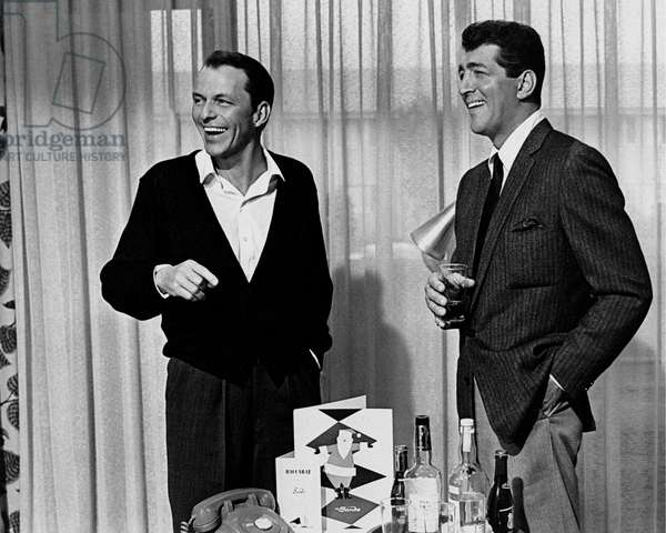 Dean Martin and Frank Sinatra smile in front of a table with bottles of spirit, United States