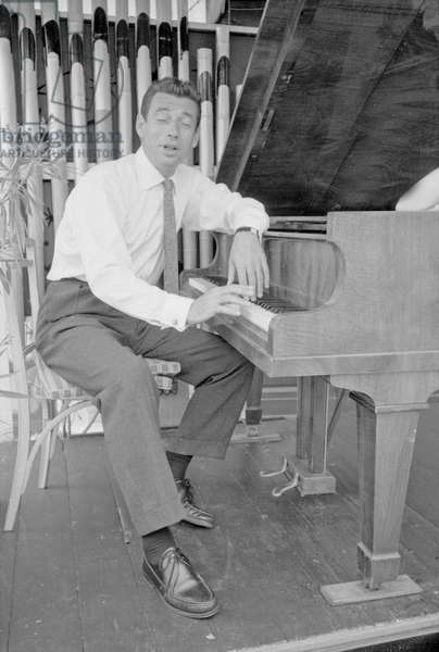 Yves Montand playing the piano, Italy, 1955 (b/w photo)