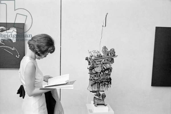 A woman reading a guide beside a sculpture by Jean Tinguely at the 32nd Art Biennale, Venezia, Italy, 1964 (b/w photo)