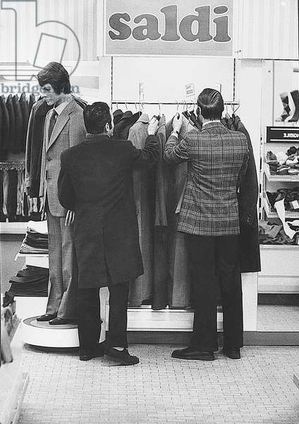 Men watching some coats on sale in a shop, Milan, January 1973 (photo)