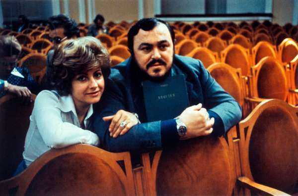 Luciano Pavarotti embraced by his wife Adua Veroni, sit in theatre seats, Italy