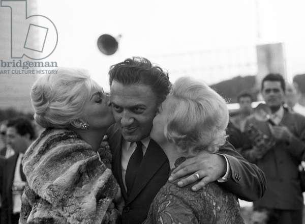 Giulietta Masina and Anita Ekberg kissing Federico Fellini, Italy, 1961 (b/w photo)