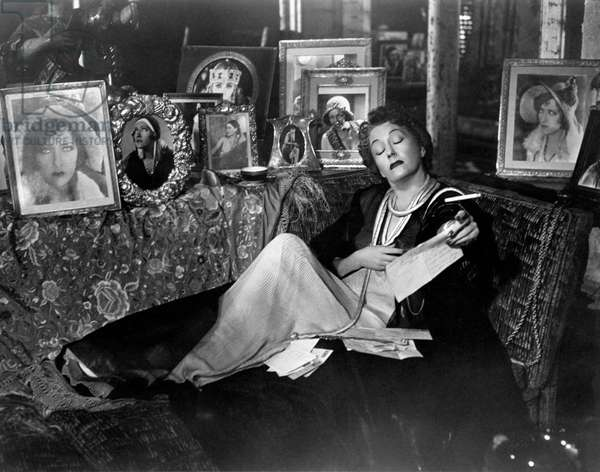 Gloria Swanson lying on the sofa reading a letter
