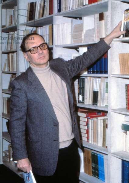 Ennio Morricone beside a bookcase, 1980 (photo)