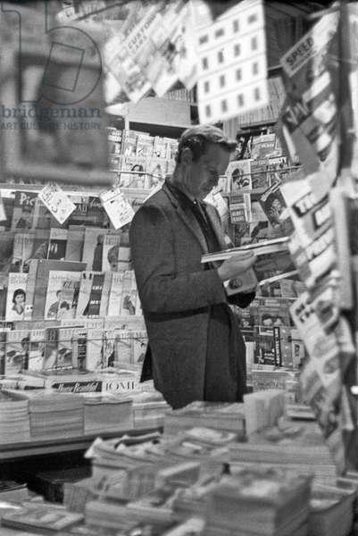 Charlton Heston leafing through a magazine, Rome, Italy, 1958 (b/w photo)