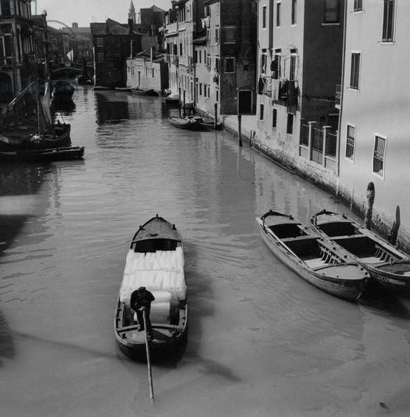 A boat carrying ice in a canal, Chioggia, Italy, March 1954 (b/w photo)