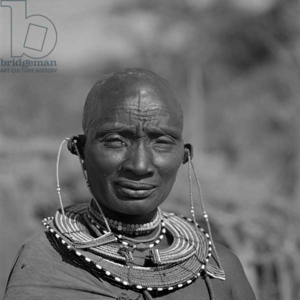 Old Maasai woman posing nearby Nairobi, Africa, April 1965 (b/w photo)